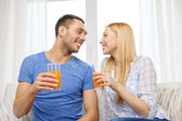 Smiling happy couple at home drinking juice — Stock Photo