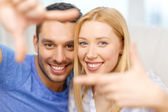 Smiling happy couple making frame gesture at home — Stockfoto