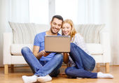 Smiling happy couple with laptop at home — Stockfoto