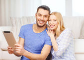 Smiling happy couple with tablet pc at home — Stock fotografie