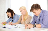 Tired students with notebooks at school — Stock Photo