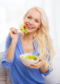 Smiling young woman with green salad at home — 图库照片