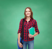 Smiling female student with bag and notebooks — Stok fotoğraf