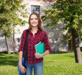 Smiling female student with bag and notebooks — Foto Stock