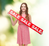 Jovem mulher vestida com um sinal de venda — Fotografia Stock