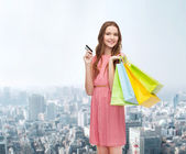 Smiling woman in dress with many shopping bags — Foto de Stock