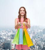 Smiling woman in dress with many shopping bags — Стоковое фото