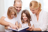 Smiling family and two little girls with book — Stock Photo
