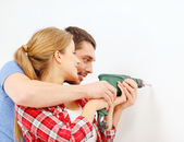 Smiling couple drilling hole in wall at home — 图库照片
