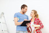 Smiling couple with clipboard and wallpaper roll — Stock Photo
