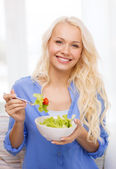 Smiling young woman with green salad at home — Stockfoto