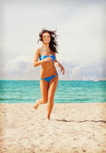 Happy smiling woman jogging on the beach — Foto de Stock