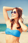 Happy woman in sunglasses on the beach — Stok fotoğraf