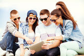 Group of teenagers looking at tablet pc — Stockfoto