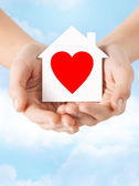 Hands holding white paper house — Stock Photo