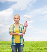 Sonriente en guantes con rodillo de pintura — Foto de Stock