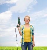 Smiling woman with drill machine — Stockfoto