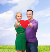 Smiling couple holding big red heart — Стоковое фото