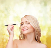 Beautiful woman with closed eyes and makeup brush — Stok fotoğraf