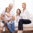 Smiling parents and two little girls at new home — Stock Photo