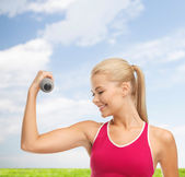 Young sporty woman with light dumbbell — Stockfoto