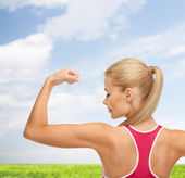 Sporty woman showing her biceps — Stock Photo