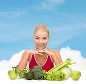 Smiling sporty woman with organic food — Stock Photo