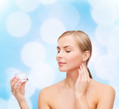 Woman applying cream on her skin — Stockfoto