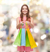 Smiling woman in dress with many shopping bags — Stock fotografie