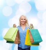 Smiling woman with many shopping bags — Stok fotoğraf