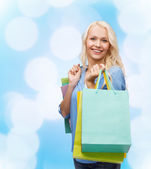 Smiling woman with many shopping bags — Stock fotografie