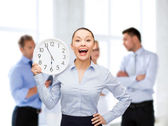 Attractive businesswoman with wall clock — Stok fotoğraf