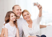 Happy family with little girl making self portrait — Stock Photo