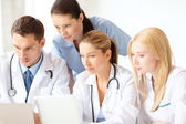 Group of doctors with laptop and tablet pc — Stock Photo