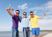 Friends having fun on beach with bottles of beer — Stock Photo