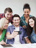 Students looking into smartphone at school — Stock Photo