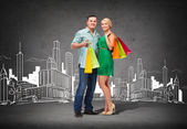 Smiling couple with shopping bags — Stock Photo