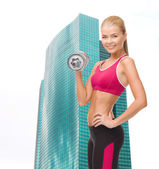 Smiling woman with heavy steel dumbbell — Stockfoto