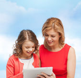 Smiling mother and daughter with tablet pc — Stock Photo