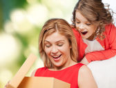 Smiling mother and daughter opening gift box — Stock Photo