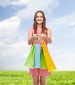 Smiling woman in dress with many shopping bags — Photo