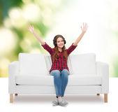Teenage girl sitting on sofa with headphones — Stock Photo