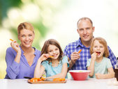 Happy family with two kids eating at home — Stock Photo