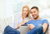 Smiling happy couple with tablet pc at home — Stock Photo