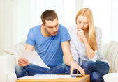 Busy couple with papers and calculator at home — Stock Photo