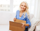 Smiling young woman opening cardboard box at home — ストック写真