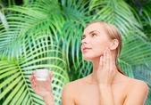 Woman applying cream on her skin — Stock Photo