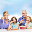 Happy family with two kids eating at home — Stock Photo #43759381