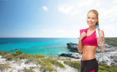 Sporty woman with bottle of water and towel — Stock Photo