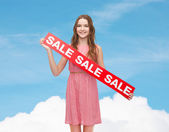Young woman in dress with sale sign — Stock Photo